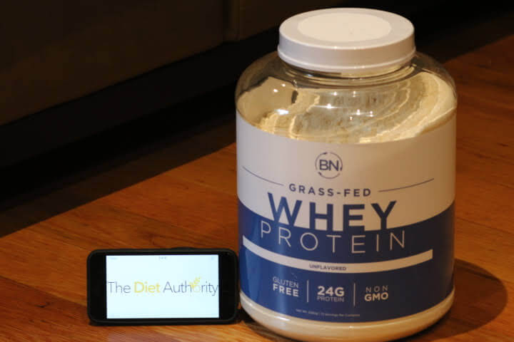 A 5lb Container of BN Labs Grass-Fed Unflavored Whey Protein next to iPhone displaying The Diet Authority website logo