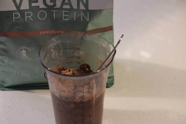 BN Labs Vegan Chocolate Protein Powder in a mixing cup with a fork